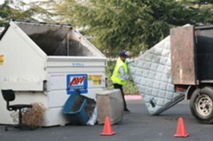 worker disposes of a mattress at an apartment complex in Redwood City