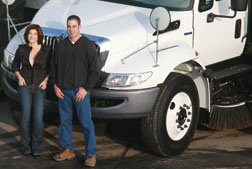 Owners of Universal Site Services in front of a sweeping truck.