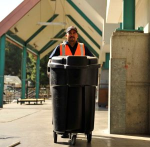 Reseda day porter pushing a trash can